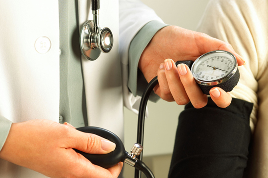 A doctor reading a blood pressure gauge