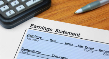 A calculator and an earnings statement